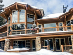 """""""Yard art"""" sculptures on the decks and front yards of multi million dollar homes along Last Chance Run at Deer Valley Resort. Here, the home sports carved bears, two of them 'skiing' along the roof and decks."""