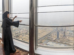 Local women wearing traditional Muslim burka robes view the city of Dubai from the top of the Burj Khalifa, world's tallest building.