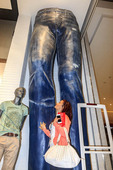 Local woman shopper poses near a pair of giant jeans pants in Dubai Mall
