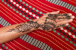 Colorful and intricate henna tattoo on a woman's hand and arm.