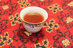 Cup of Arab tea against a colorful rug.