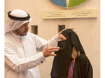 Culture center guide helps visitor try on Muslim robe.