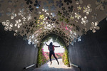 "Reflective tunnel ""flowers"" reflect the real flowers outside as a visitor jumps in air at Dubai's Miracle Garden"