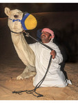 Bedouin man in traditional Arab dress with his camel.