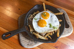 Fraser Valley Poutine made with duck confit, cheese curds, French fries and topped with two sunnyside up eggs.