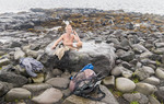 Local man bathes in a natural hot spring set in rocks at Reykjavik's waterfront