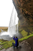 Visitor photographs Seljalandsfoss, a spectacular waterfall that falls 213 feet (65 metres) over an old sea cliff. It is just off the Ring Road in southern Iceland.  A short path takes people behind the falling water.
