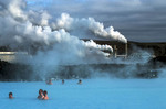 People relax in Iceland's Blue Lagoon with power plant in background.