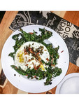 Grilled kale and fried egg with crispy prosciutto served at Juniper, a restaurant in Boise, Idaho.