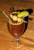 Caesar drink made with clamato juice, vodka, tabasco, rimmed with celery salt and topped with olives.