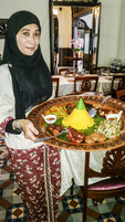 Waitress brings out a platter of Malay food at Mamanda restaurant in the Kampong Glam (Arab) district of Singapore.
