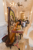 Woman plays harp during high tea in Raffles Hotel.