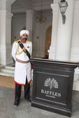 Sikh doorman at entrance to Singapore'a Raffles Hotel