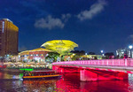 Singapore's popular nightspot, Clarke Quay, at night, lit in shifting colors.