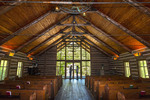 Inside the Hope Wilderness Chapel, a replica of an 1880s chapel, on the ground of the Dogwood Canyon Nature Park near Branson, MO. It is a popular spot for marriage ceremonies. Here a man and women hold hands by the window.