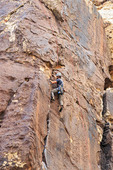 Climber scales rock in Red Rock Canyon National Conservation Area, 20 miles west of  Las Vegas, NV, USA.