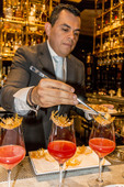 Mixologist creates a Billini Rosso, a fancy alcoholic drink featuring various liquors, juices, a caramel nest and a gilded raspberry,