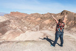 Young woman excitedly enjoys the view from Death Valley's famous Zabriskie Point of surrounding desert hills.