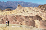 Young couple enjoys the view from Death Valley's famous Zabriskie Point of surrounding desert hills.