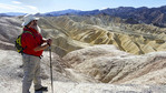 Man enjoys view from Death Valley's famous Zabriskie Point of surrounding desert hills.