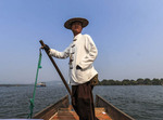 Boatman rows boat during tour on West Lake in Hangzhou, China.