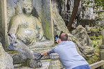 Visitor takes picture of Buddha statue while rubbing the statue's foot at Lingyin Temple in Hangzhou, China.
