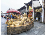 Buddha statue at start of Qinghefang Ancient Street, which is lined with shops and snack stands in Hangzhou, China.