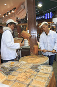 Men pound sesame seeds into flat paste which is then made into candy in a shop along Qinghefang Ancient Street, in Hangzhou, China.