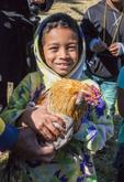 Victorious young boy chicken catcher during Mardi Gras Chicken Run