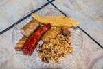 Plate of Cajun food including fried catfish, sausage, boudin, cracklins and dirty rice.