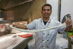 Owner/cook Duan Ya Min makes fresh noodles at Xi An Cuisine in Richmond Public Market, Richmond, BC, Canada