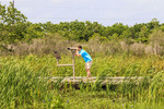 Visiting man looks at marsh through telescope on boardwalk that is part of the Cameron Prairie National Wildlife Refuge Pintail Drive.