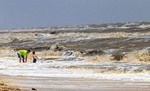 Young boy plays in rough surf with father during a windy day at Rutherford Beach on the Gulf of Mexico coast in Louisiana.