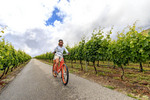 Woman gets ready to ride through grape vineyard on an electric assist bicycle in Oliver, southern Okanagan Valley, BC, Canada.