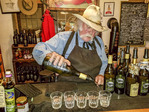 Owner Bruce Fuller pours wine at cowboy themed Rustico Farm & Cellars winery in Oliver, southern Okanagan Valley, BC, Canada.