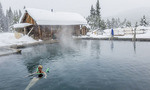 Woman soaks in the 100 degree water of the main pool at Burgdorf Hot Springs during a light snowfall.
