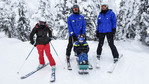 "Archie, 11, in a ""sit-ski"" for paralyzed skiers with volunteer skiers as part of Big White Ski Resort's adaptive ski program for disabled skiers."
