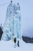 Father and son check out the 60 foot tall ice climbing tower in Happy Valley Adventure Park at Big White Ski Resort.