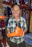 Dizzy of Dizzy's boot fitting shop at Big White ski resort shows off a 1970s ski boot,