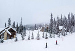 Skiers come down to the Big White Ski Resort village at the end of a snowy day with great powder.