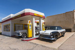 Vintage gas station complete with old cars, pumps and ads, on the outskirts of Bisbee, AZ.