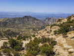 View from Windy Point, along the road up Mount Lemmon. Three people on rock admire view.