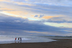 Boys play on the beach at Seaside, Oregon, at sunset.
