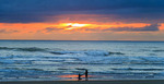 People walk the beach at Seaside, Oregon, at sunset.