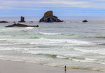 Surfers walk out to surf and return, seen from Indian Beach Trailhead, the start of the Clatsop Loop trail at Ecola State Park in Oregon, USA.