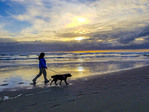 Woman and her dog walk the beach at Seaside, Oregon, at sunset.