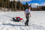 Towing tent and gear out on lake for ice fishing on Heffley Lake near Sun Peaks Resort with Elevated Fishing Adventures.