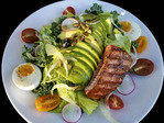 Sockeye salmon in a Cobb salad with greens, avocado, pumpkin seed, egg.