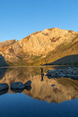 Man walks out on rocks to photograph Convict Lake near Mammoth Lakes, California at dawn. It REALLY is this color at dawn.
