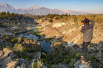 Man photographs Hot Creek in early morning at Hot Creek Geological Site near Mammoth Lakes, California.